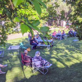 Community enjoying picnic in Park litening to music